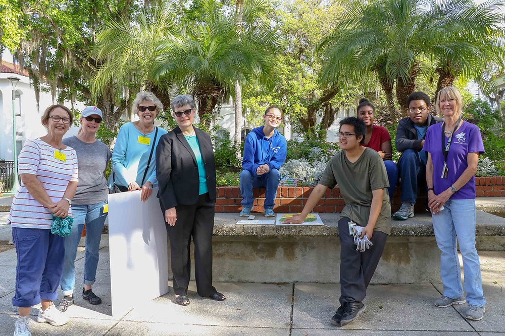 Members of the Las Adelfas Circle Garden Club and FSDB D&B Garden Center students in front of plants.