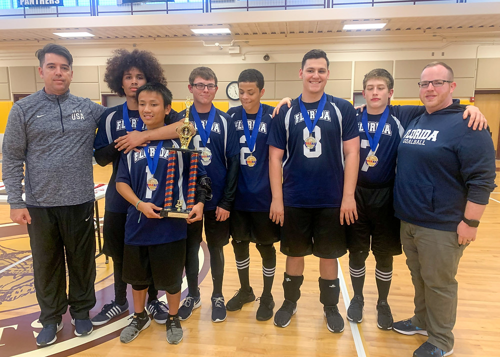 FSDB Boys Goalball team wearing gold medals and holding first place trophy.