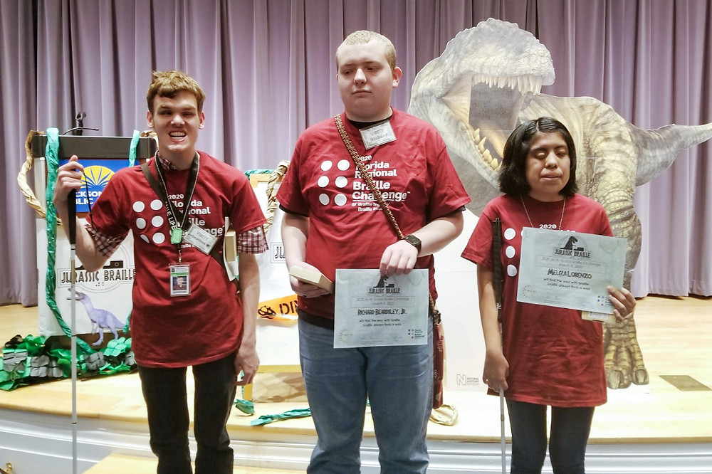 Johnathan, Richard and Meliza holding their certificates at the front of the stage.