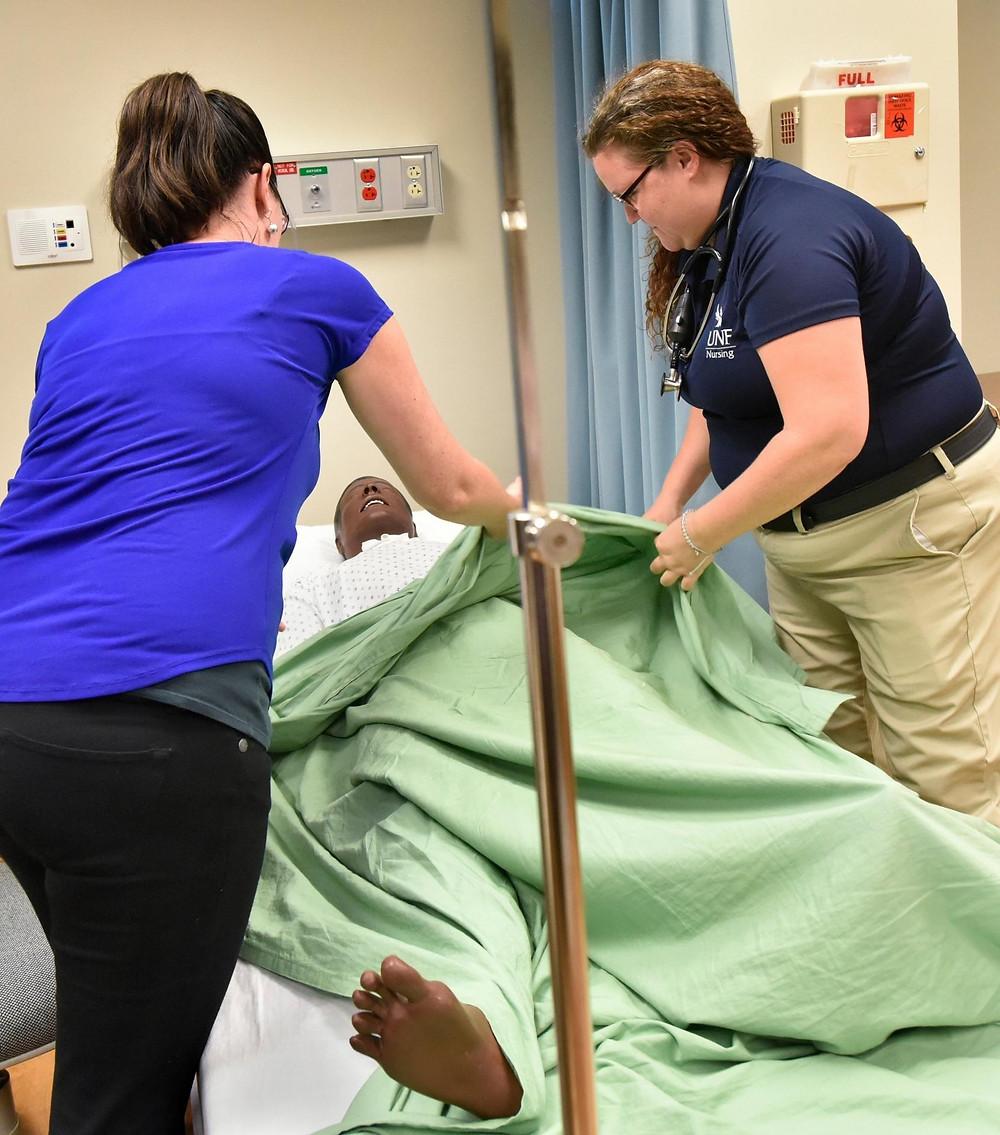 Professor of nursing Cora Evensen (left) and deaf nursing student Bethany (Bebe) Baker make up a medical mannequin's bed.