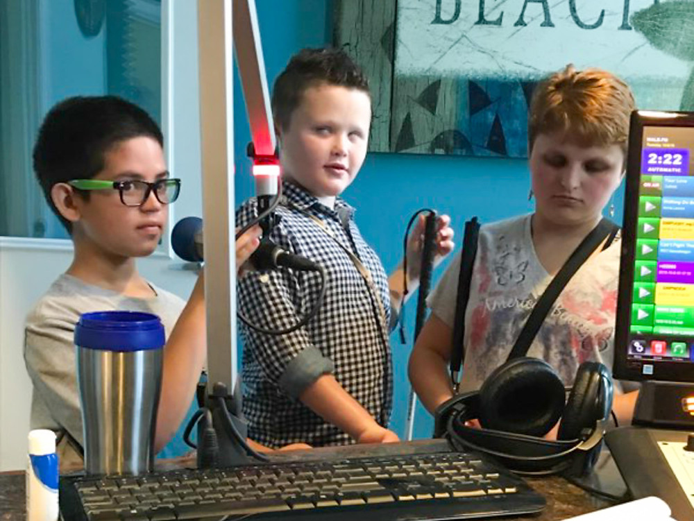 Nathaniel, Logan, and Gracie speak into microphone at radio station.
