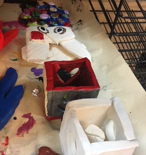 Clay artwork on a table, designed as birdhouses and an owl.