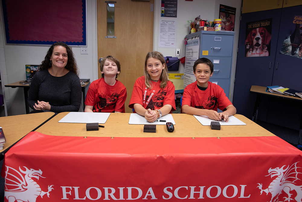 "Three students and a teacher from the ""Blue"" team sit a table and smile at camera."