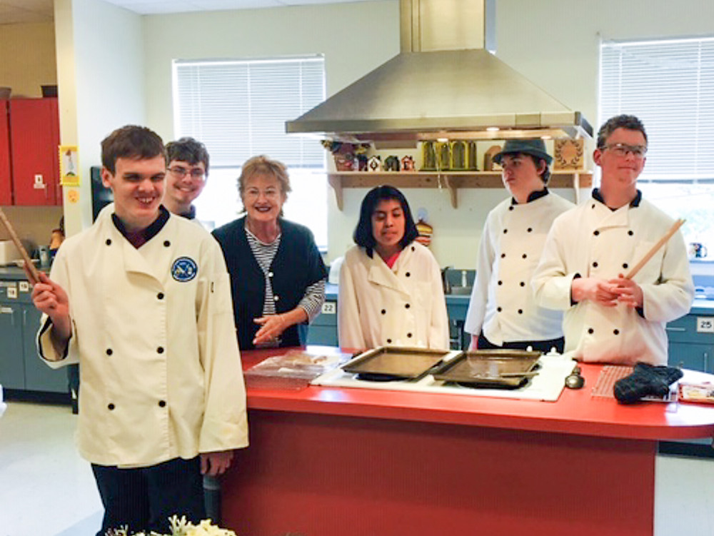 Ms. Parsons with class in front of stove top.