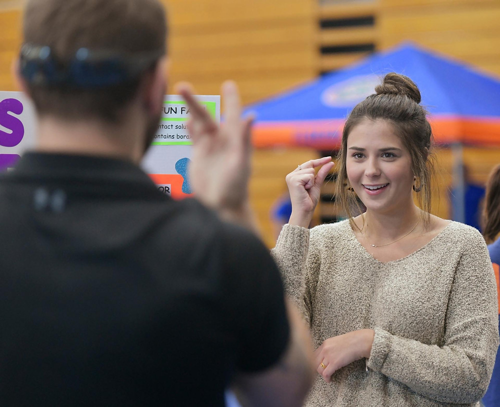 Two UNF students communicating using sign language.