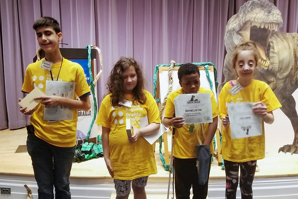 Damian, Janna, Khayree, and Danika holding their certificates at the front of the stage.