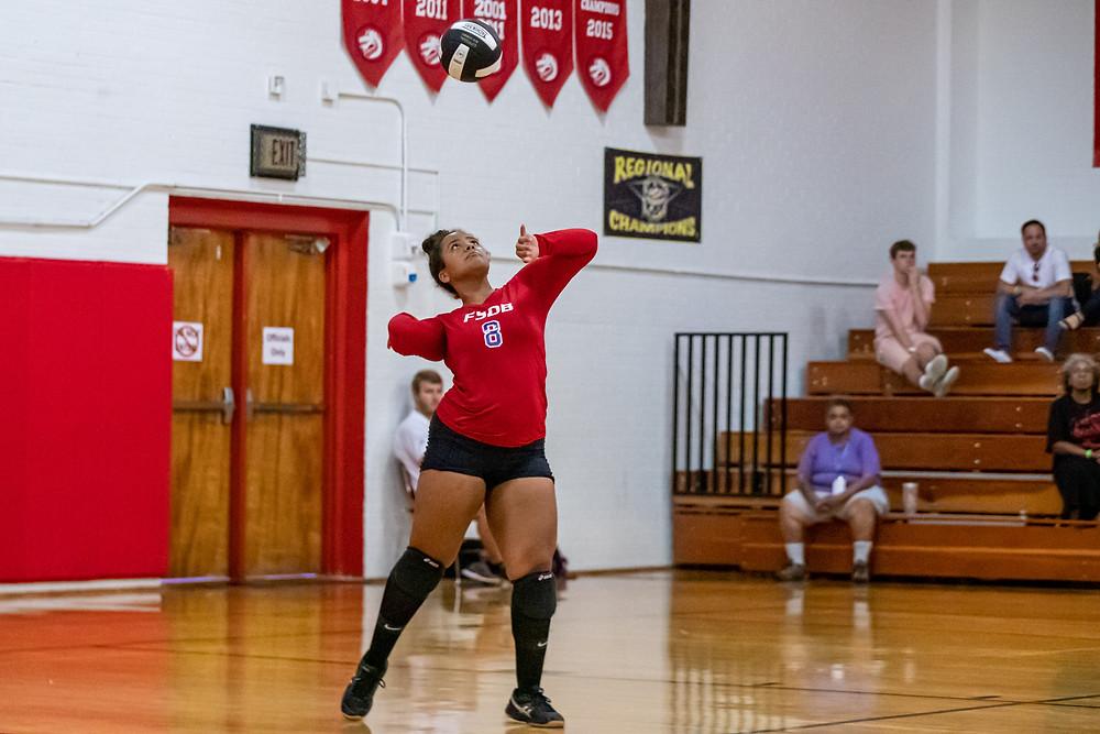 Brieara serving the ball during a volleyball match.