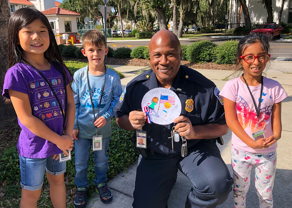 Three elementary students give an veteran's appreciation gift to an FSDB police officer.