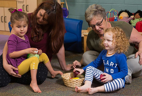 Two blind girls and two teachers in the FSDB todller program sit on floor and play with toys.