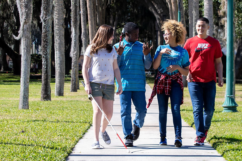 Two blind and two deaf students walking down Palm Row.