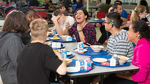 Students laughing while eating lunch.