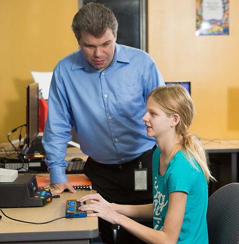 FSDB blind girl uses Smart Brailler while teacher looks on.