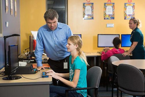 FSDB teacher helps blind student using Smart Brailler in the library.