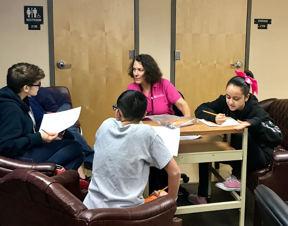 Amy Moring works with three blind middle school students on how to write grants.