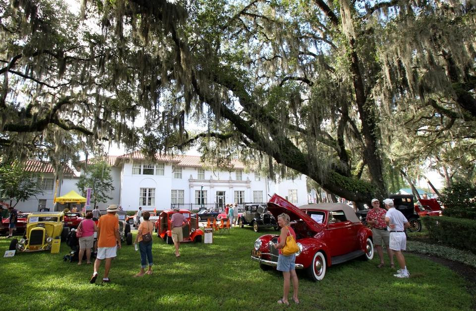 Spectators look at classic automobiles parked in the grass on the FSDB campus.