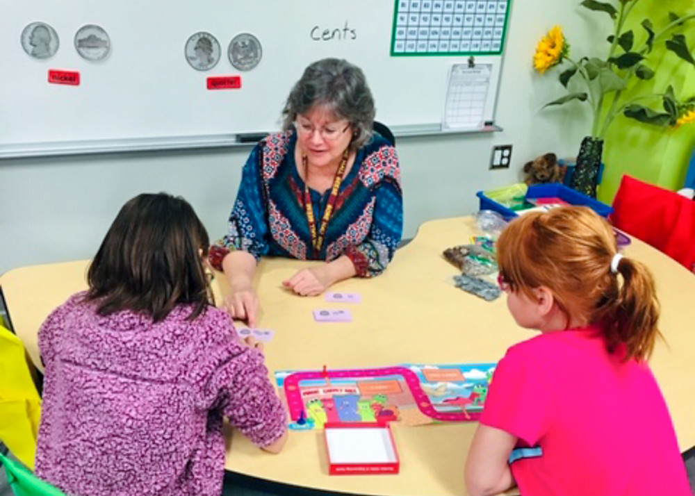 FSDB DES teacher Marla Hilliard working with two students.