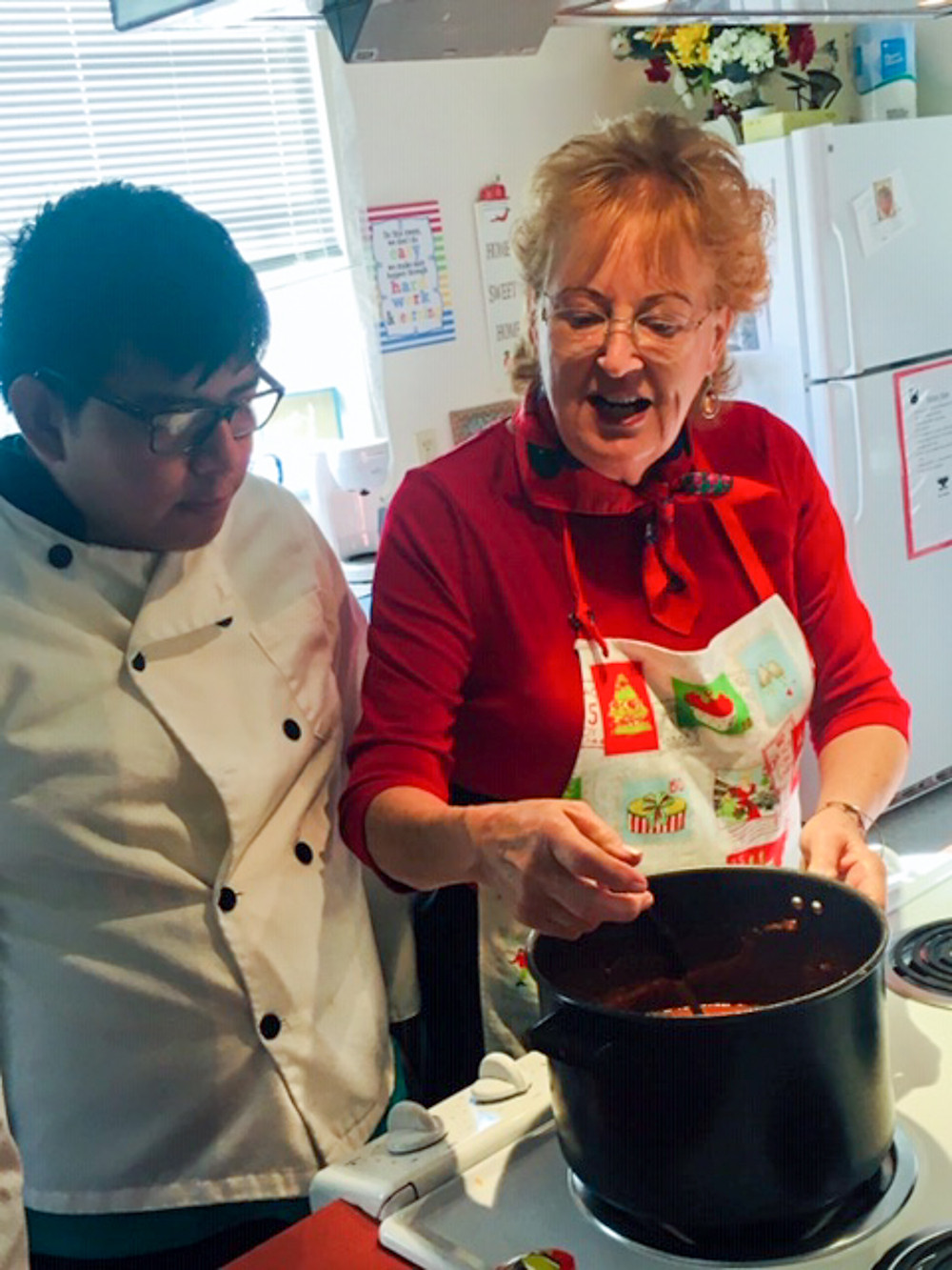 Ms. Parsons teaching a blind student how to cook spaghetti sauce.