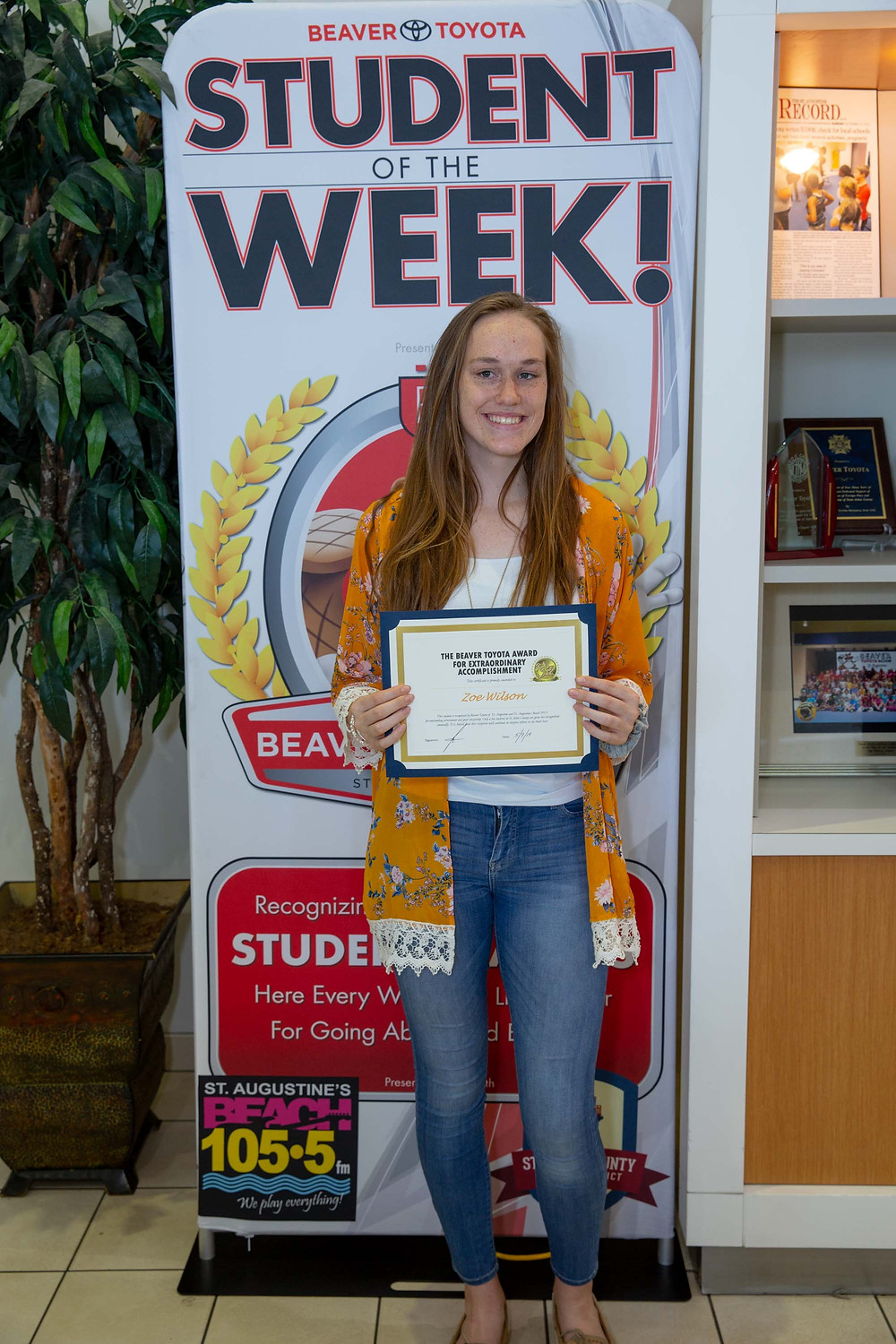 Zoe Wilson holding Student of the Week certificate in front of Beaver Toyota banner.