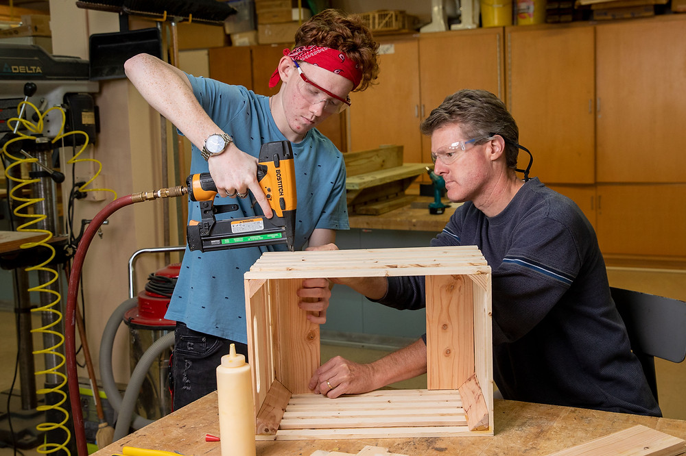 Brendan Fadden uses a nail gun to put together a box while Randall Hancock holds it in place.