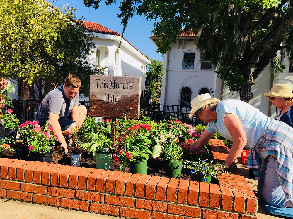 FSDB student and Las Adelfas member plants flowers on FSDB campus.