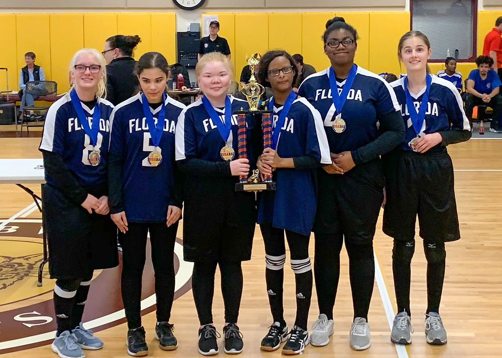 FSDB Girls Goalball team wearing gold medals and holding first place trophy.