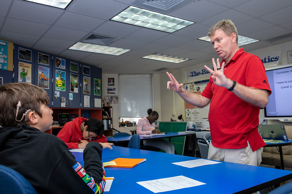 Matt Smith holding his hands up with the numbers 4 and 3 while a student looks on.