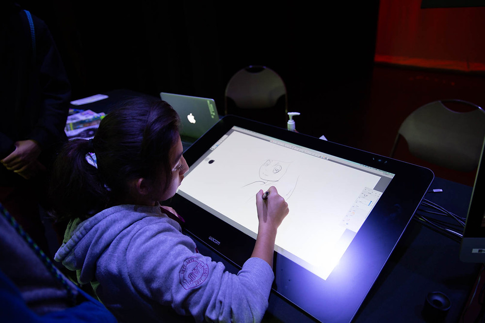 Girl drawing animated girl on digital tablet at the FSDB CTE Expo.