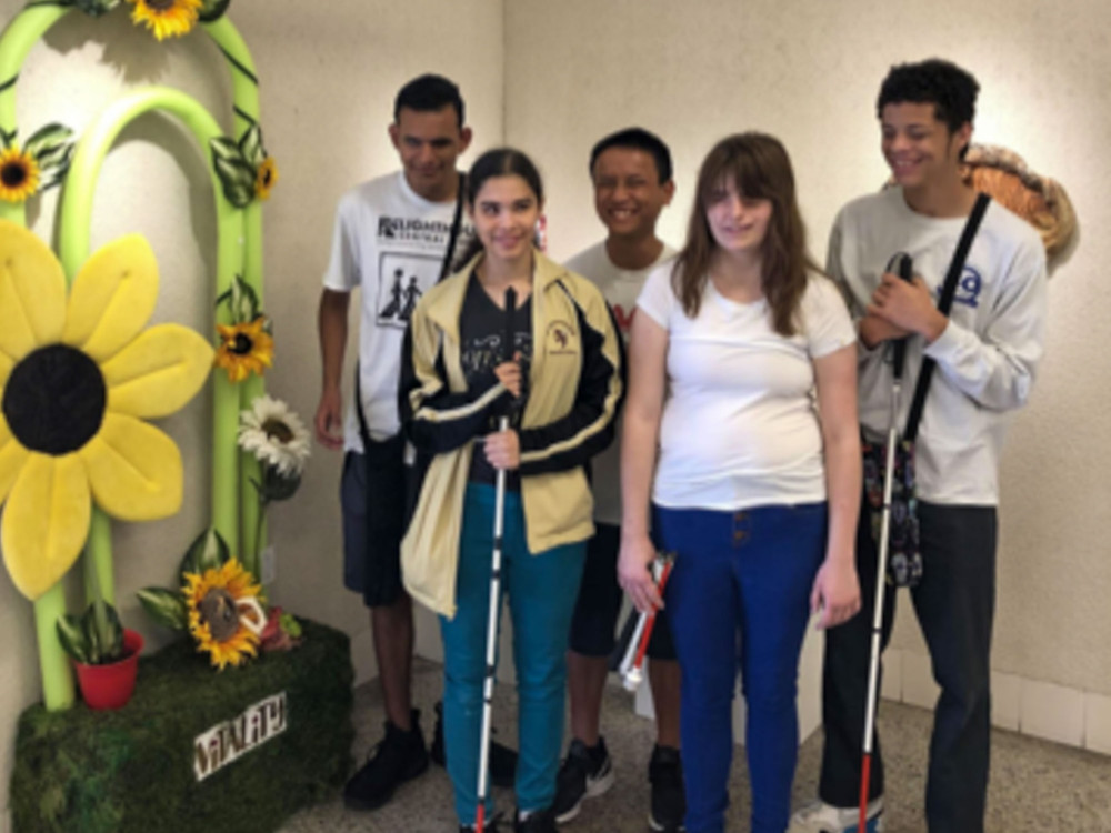 Five blind students stand in front of Flower Artwork at Tactile Art Show.