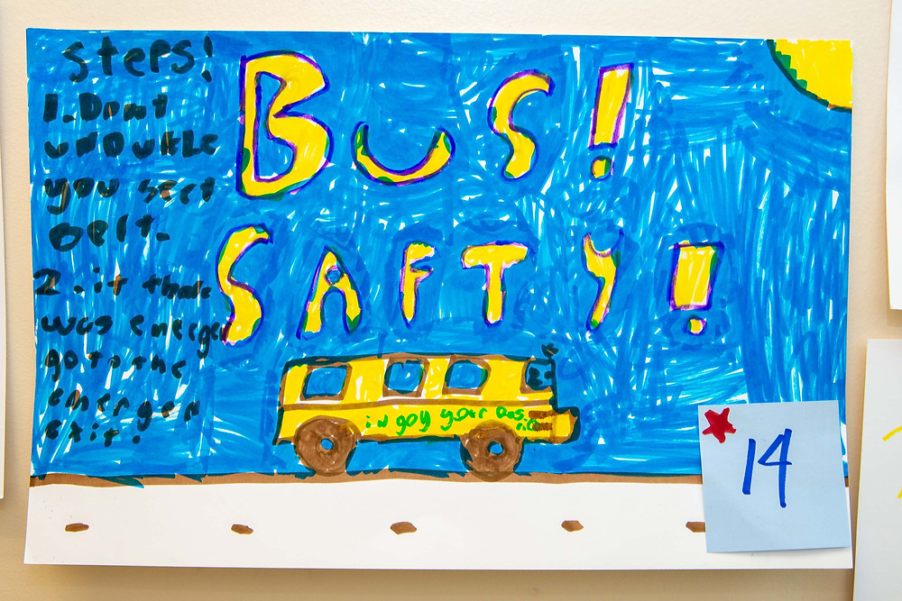 Hand drawn bus safety poster; yellow bus on a blue background with the words Bus Safety above it.