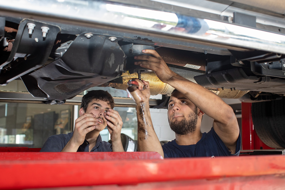 Luis and a co-worker change the oil underneath a truck.