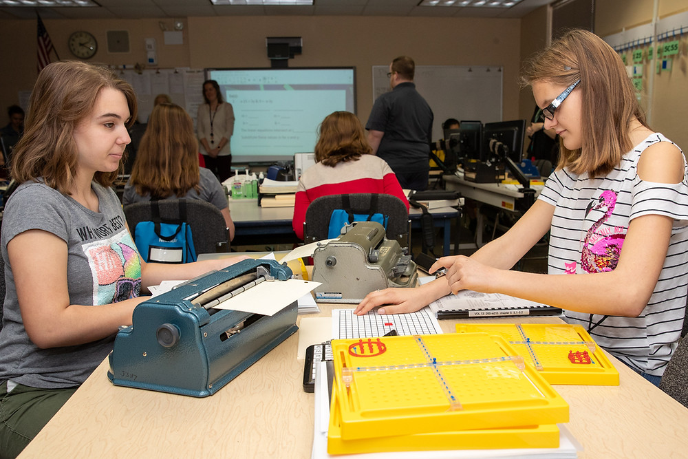 Two blind girls work on math problems using braillers.