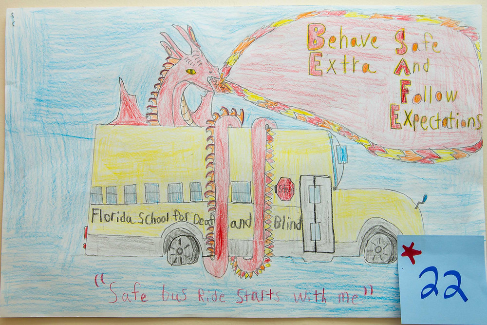 "Yellow bus with red dragon wrapped around it. Reads ""Behave extra safe and follow expectations."