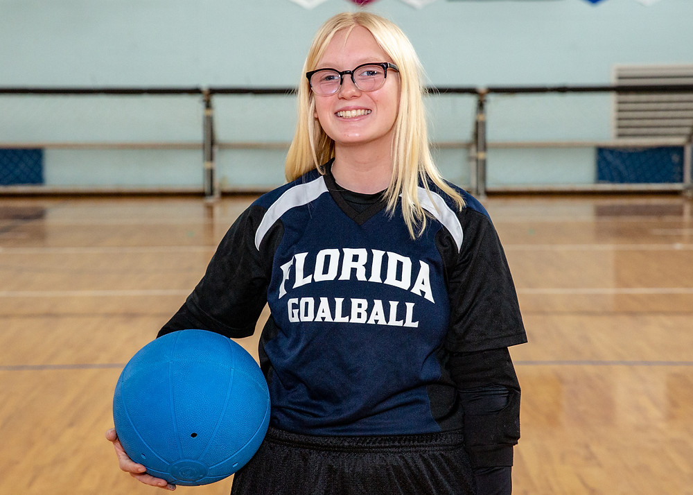 Veronica wearing her Goalball uniform and holding a ball.