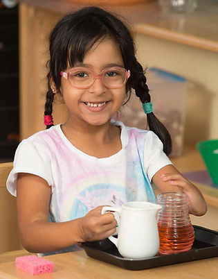 Deaf elementary girl with glass pouring liquid from a small pitcher into a glass.