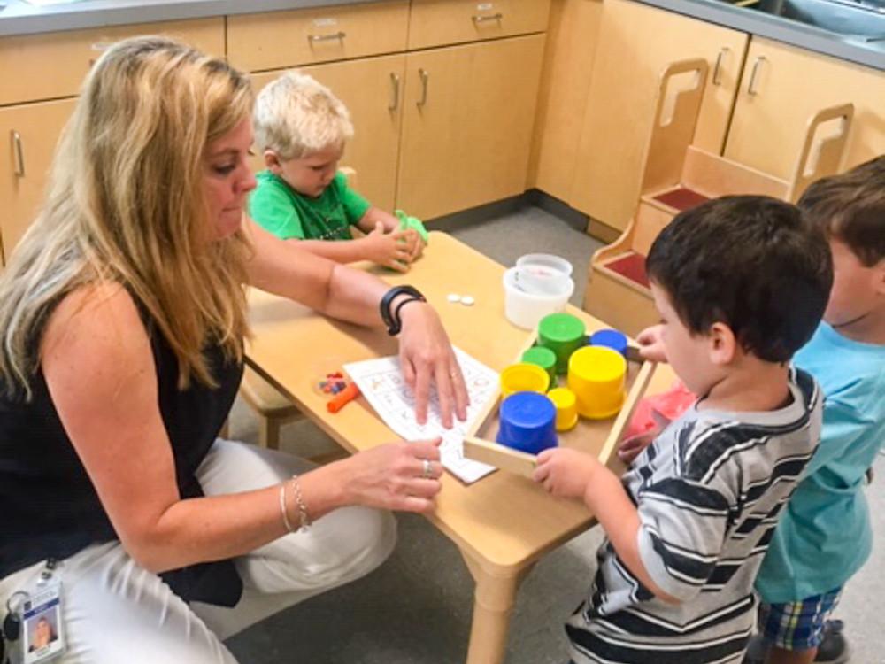 FSDB ELC teacher Dawn Parke teaching 3 deaf boys about colors.
