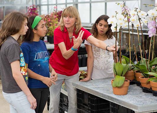 FSDB horticulture teacher showing three deaf girls an orchid.