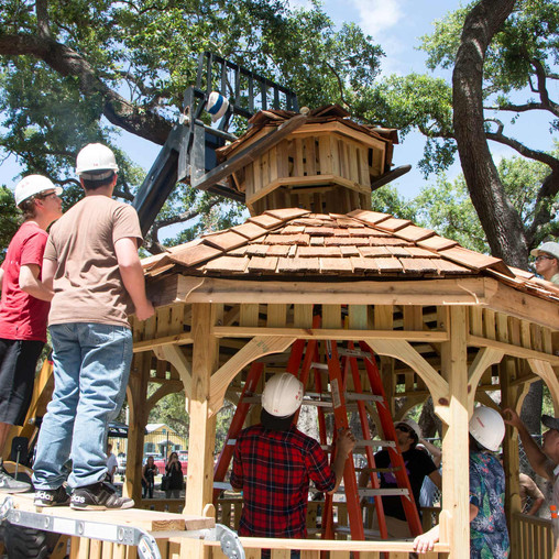 FSDB students watch as a forklift places the cupola on top of the gazebo.