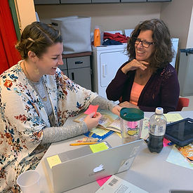 Two teachers using sticky notes in a book.