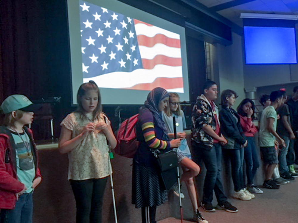 FSDB Blind Middle School students stand in front of stage with American Flag on projection screen behind them.