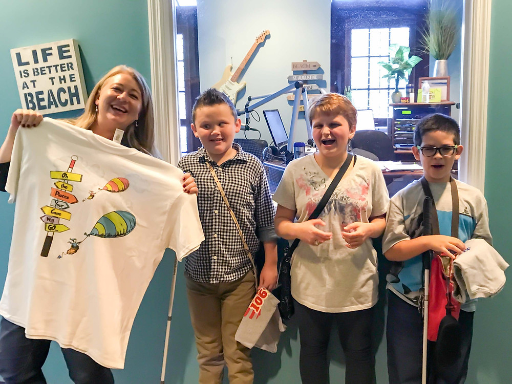 FSDB students Logan, Gracie, and Nathaniel pose for photo with Kandi Lowe who is holding a White Cane Day t-shirt.