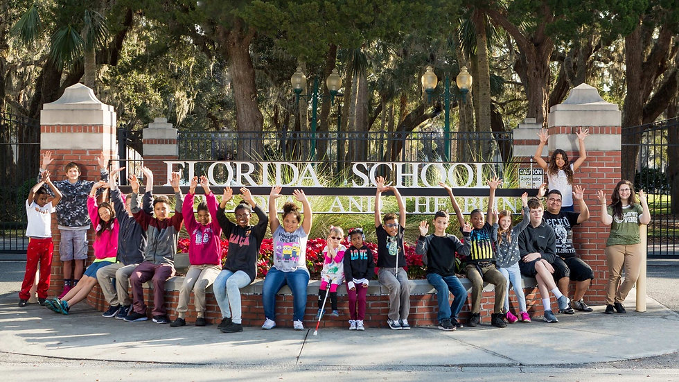 FSDB students sitting around the FSDB sign at the front gate.