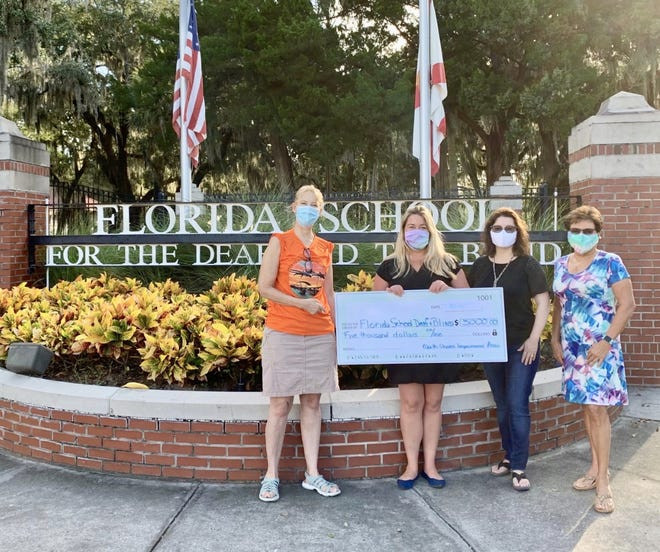 Jean Miller, Amy Gilbert and Fran Windeler gives a $5,000 check to Tanya Rhodes in front gate of FSDB.