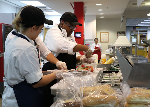 Two students prepare food in the Dragons Lair Cafe.