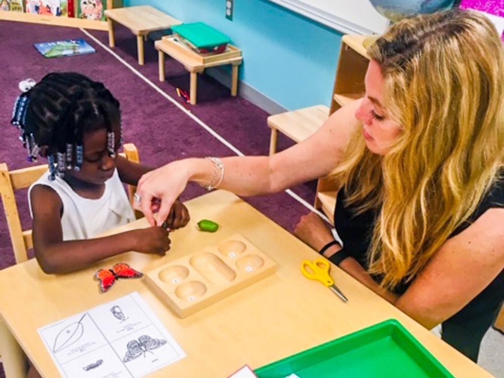 FSDB ELC teacher Dawn Parke teaching deaf girl about butterflies.