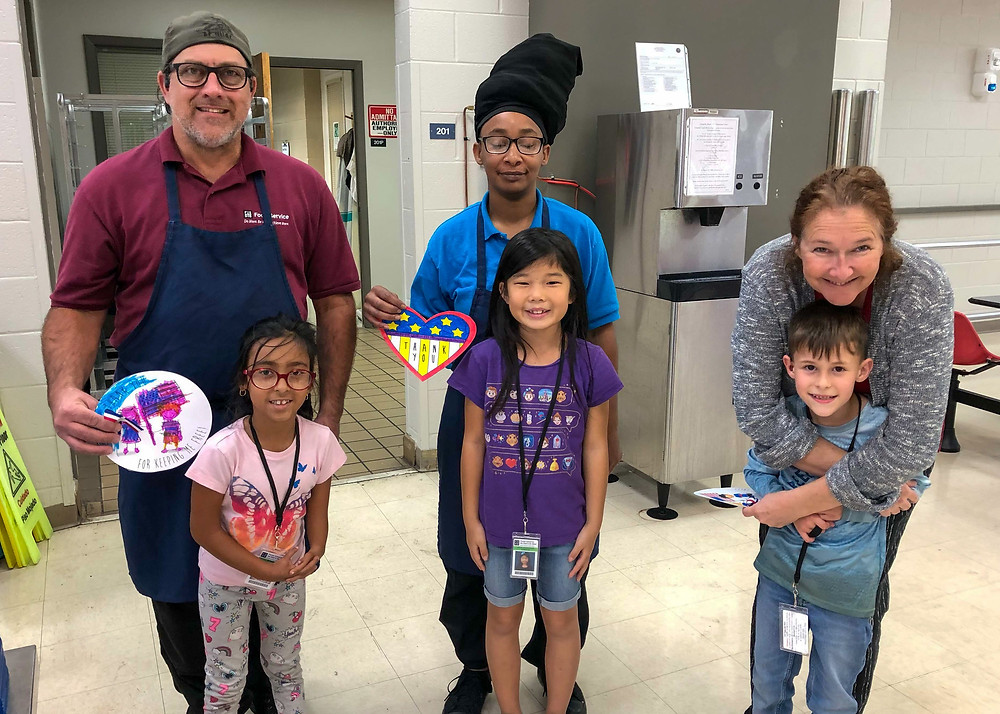 Students give three food service employees thank you gifts.