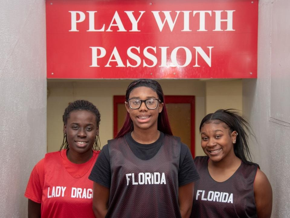 Lourdine Jordonee, Olivia Brown, and Keliah Williams standing in front of Play with Passion sign.