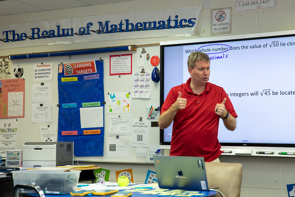 Matt Smith standing in front of a whiteboard explaining a math problem.