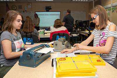 Two blind middle school girls using braillers in math class.