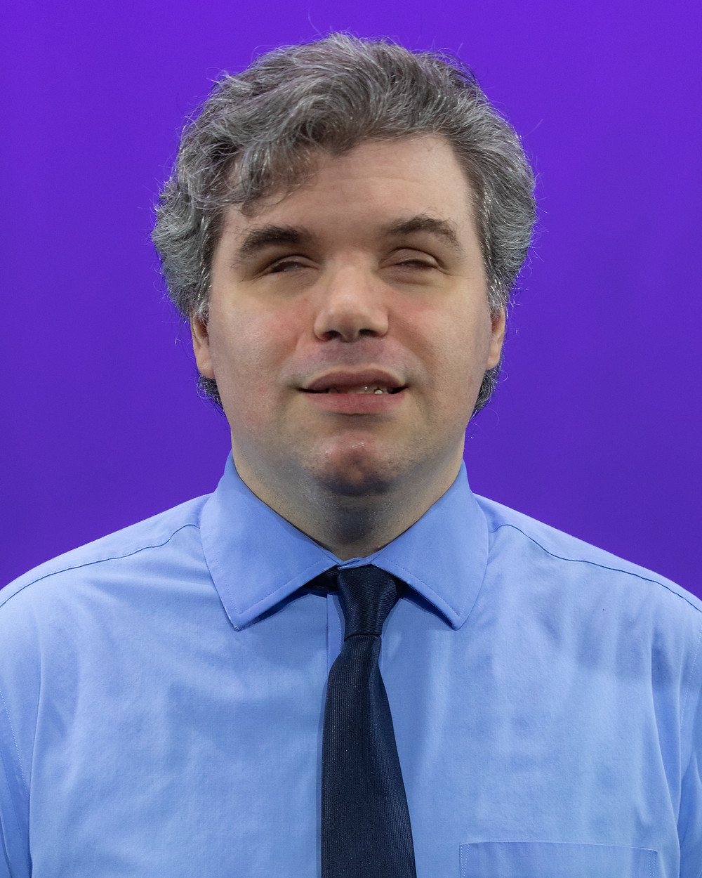 Patrick Turnage in blue shirt and tie in front of a purple background.