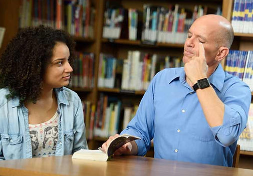 FSDB librarian signing to deaf student in library.